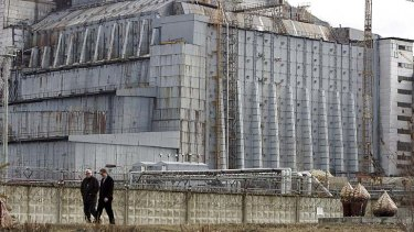 Workers walk in front of the fourth reactor at the Chernobyl.