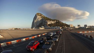 Drivers wait in line along the road of the Gibraltar International airport to enter to Spain at its border with the British territory of Gibraltar.