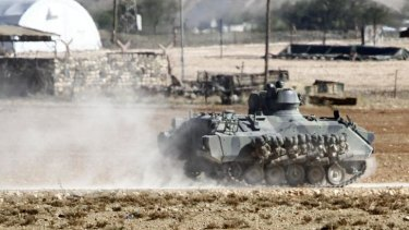 A Turkish tank manoeuvres near the Turkish-Syrian border. Turkey is now allowing Kurdish forces to be reinforced in Kobane through its border with Syria.