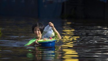A Thai woman makes her way through floodwaters on the outskirts of Bangkok last month.