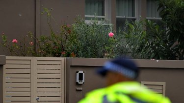 A police officer stands in front of two bullet holes - one on the wall near the downpipe on the left, and the other on the top of the fence on the right - outside a house in Harris Street, Merrylands.