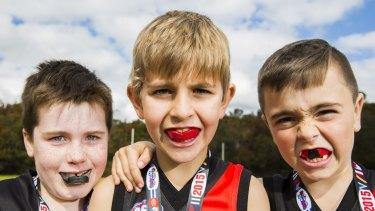 Conor Ferron, 7, James Rudzis, 8  Jairus Brealey, 8. (L to R) were wearing mouthguards when they played at a gala day to mark the end of the AFL Auskick season at Waratah Park Reserve, Sutherland.