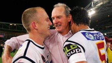 Wayne Bennett celebrates the Broncos's 2006 Grand Final win with  Darren Lockyer and Karmichael Hunt.