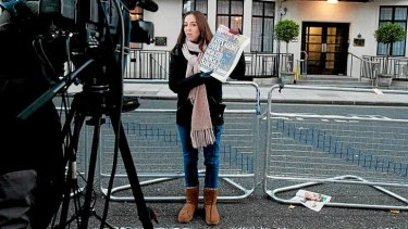 A broadcast journalist holds up a copy of a daily newspaper outside the King Edward VII hospital in central London after nurse Jacintha Saldanha was found dead the previous day.