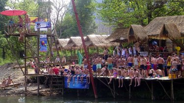 Tourists crowd a riverside bar in Laos, by one of the diving towers.