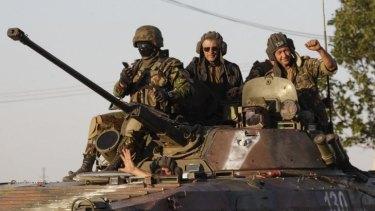 Ukrainian servicemen ride on an armoured vehicle in Mariupol following the ceasefire.