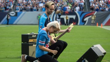 Meghan Linsey kneels after singing the national anthem before the start of the Tennessee Titans and Seattle Seahawks football game at Nissan Stadium in Nashville on Sunday.