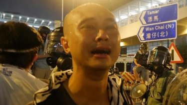 Tears of sadness: Student Leung Hei is overcome with emotion amid the crowds.