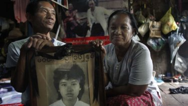 Win Kyu, left, and his wife Khin Htay Win hold a portrait of their 16-year-old daughter Win Maw Oo, who was killed during the 1988 protests. The photo behind them of their badly injured daughter came to symbolise the brutality of the crackdown.