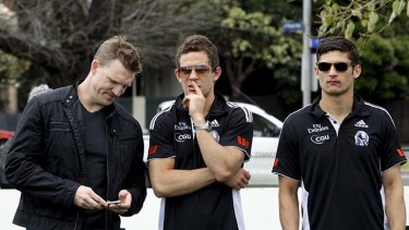 Collingwood assistant coach Nathan Buckley talks to Luke Ball and Sharrod Wellingham after the players were presented to the Magpies supporters yesterday.