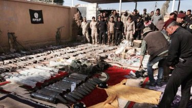 The Iraqi military displays confiscated Islamic State weapons and ammunition, with an IS flag placed upside down in the background as a mark of disrespect.