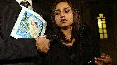 Distraught ... Lisha Barboza, daughter of dead nurse Jacintha Saldanha, leaves Britain's Houses of Parliament with father, Ben, carrying a photo of her mother.