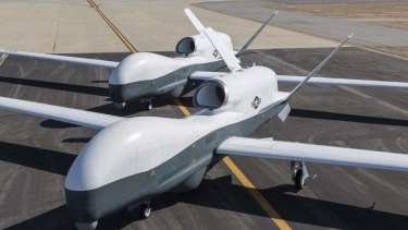 Two Northrop Grumman MQ-4C Triton unmanned aerial vehicles at a test facility in California.