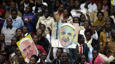 Youths hold images of Pope Francis prior to his arrival at a stadium in Nairobi.