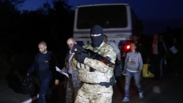 Political swap: A Ukrainian soldier guards pro-Russian prisoners-of-war during a prisoner exchange near the town of Donetsk.