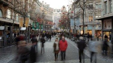 People walk down the main shopping street called the Meir in Antwerp, Belgium.