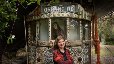 Anita Castan (front) and her daughter Karina with Mirka Mora's art tram on the family's Mt Eliza property.