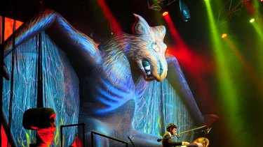 A giant bat with lasers coming from its eyes hovers over the stage.