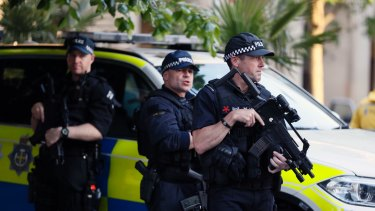 Armed police watch over a vigil in Albert Square, Manchester, on Tuesday.