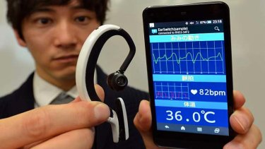 An engineer of Japanese machinery maker NS West shows the 'Earclip-type Wearable PC'.