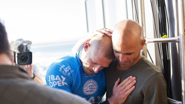 Glad you're all right: Kelly Slater embraces fellow world champion Mick Fanning.