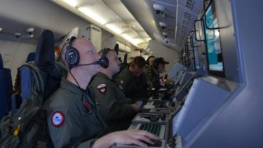 The search area widens ... A crew members on board a US Navy P-8A Poseidon at their workstations while assisting in search and rescue operations for Malaysia Airlines Flight MH370.