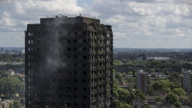 Debris hangs from the blackened exterior of Grenfell Tower in London.
