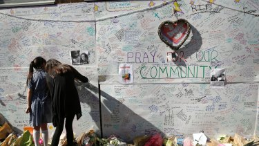 People write messages on a wall for the victims and in support for those affected by the Grenfell Tower fire.