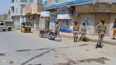 Danger zone ... Pakistani policemen and paramilitary soldiers stand on a street after gunmen shot at two buses in Quetta.