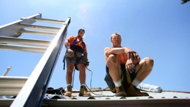High risk: One of the most dangerous and uncomfortable jobs to do on a scorching hot day - installing metal roofing.