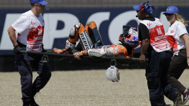 Casey Stoner, of Australia, is carried off my medical personnel after he crashed during the qualifying session for the MotoGP motorcycle race at the Indianapolis Motor Speedway.