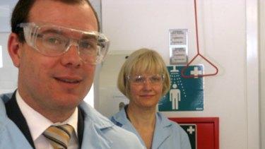 Queensland Treasurer Andrew Fraser examines one of the solar cells.