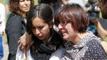 Relatives of the victims of a train accident react outside the Cersia building, where they are attended by psychologists from the Red Cross in Santiago de Compostela.