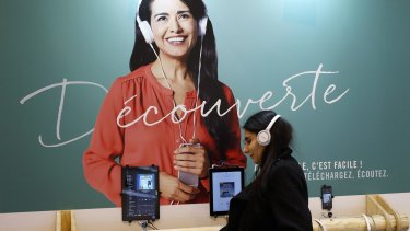 A woman listens with headphones to an audiobook during a visit to the Paris International Book Fair, held at the Porte de Versailles in Paris, France, in March.