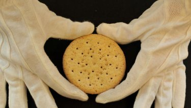 A  Huntley and Palmers biscuit from Ernest Shackleton's Nimrod store is held by a Christie's employee.