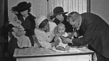 A doctor and a nurse examine a baby, while another mother waits, at a clinic (circa 1915).
