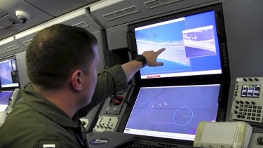 A US Navy crewman aboard a P-8A Poseidon surveillance aircraft views a computer screen purportedly showing Chinese construction on the reclaimed land of Fiery Cross Reef in the disputed Spratly Islands in the South China Sea.