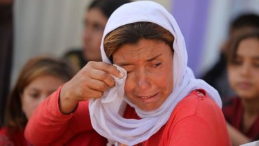 A displaced Iraqi Yazidi woman wipes her eyes.