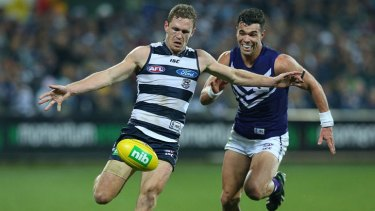 Joel Selwood, sporting a cut eye, gets a rare kick against Ryan Crowley during the Cats' win over the Dockers.