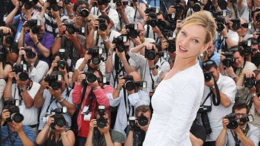 Actor and jury member Uma Thurman strikes a pose in a silk white Versace gown at the opening of the Cannes Film Festival.