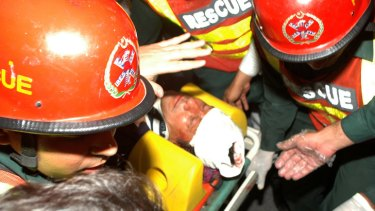 Rescue workers carry a bloodied Imran Khan to a Lahore hospital after he fell off a lift taking him onto the stage for an election rally.