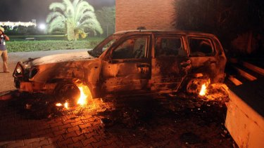 A vehicle sits smoldering in flames after being set on fire inside the US consulate compound in Benghazi.
