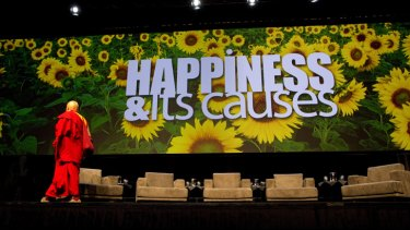 Buddhist monk, photographer, and author Matthieu Ricard leaves the stage at the happiness conference.