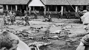 Dead Vietnamese soldiers are documented before burial.