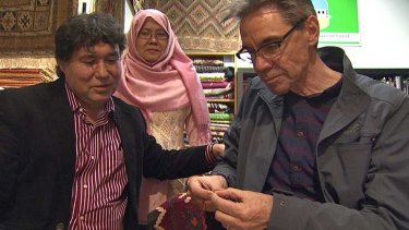 Rugmaker/author Najaf Mazari tries to teach Steve Thomas some rug repairing skills, watched by Najaf's wife Hakima.