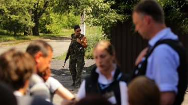 Yuri a pro-Russian rebel stands in the background as OSCE mission Alexander Hug (right) talks to residents of Rassypnoe.