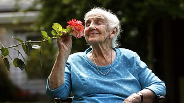 """""""As tough as old boots"""": Dame Elisabeth Murdoch enjoys the fragrant delight of the hardy rose named in her honour."""