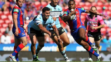 Out of reach: Newcastle's Akuila Uate evades Cronulla's Andrew Fifita.