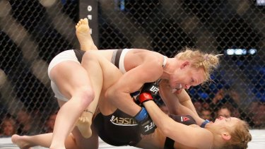 Challenger Holly Holm knocks down champ Ronda Rousey in UFC 193 at Etihad Stadium.