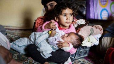 A girl holds a baby in  a family's temporary room in a refugee camp after crossing from Syria into Turkey.